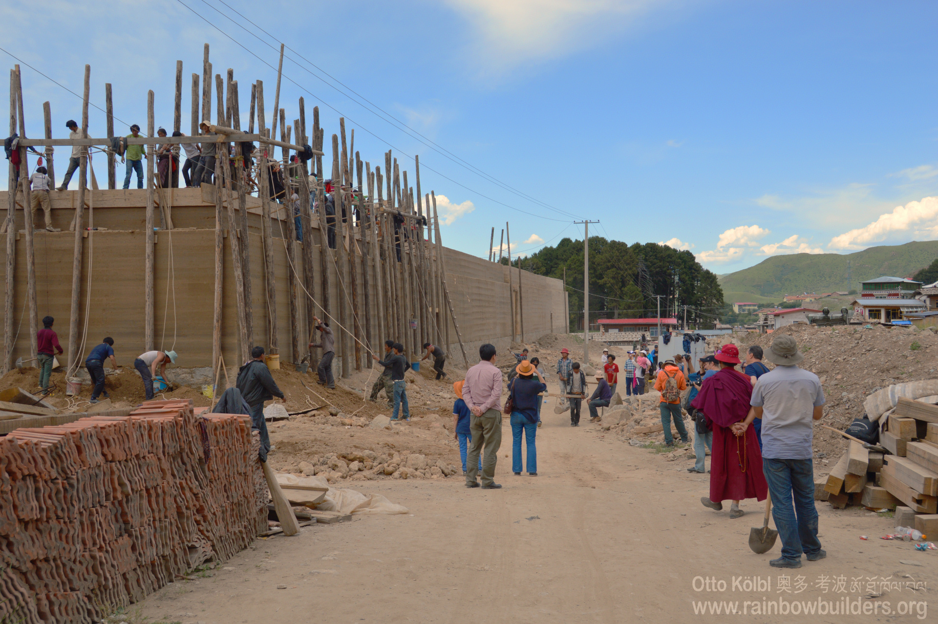 Other people below fill in buckets with earth to be lifted up. You can see the wooden framework on the top of the wall.