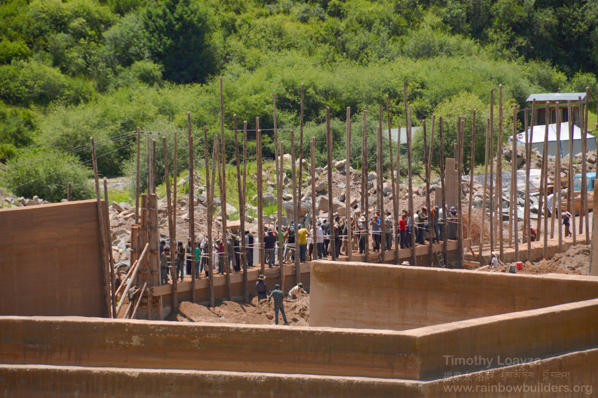 The new complex in the Lhamo Kirti monastery is made of rammed earth. The people standing on the wall are compacting the earth filled into the wooden framework using long heavy poles.